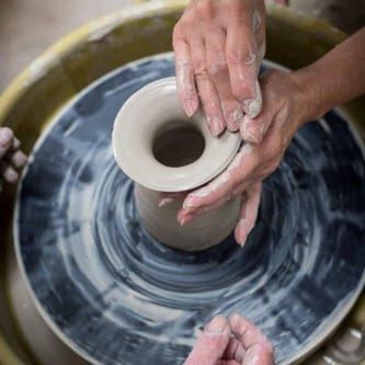A woman's hands throwing a pot on a pottery wheel