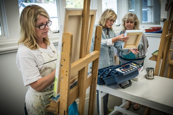 A woman paints on a canvas at an easel while another woman behind her shows a painting to instructor Victoria Wagner