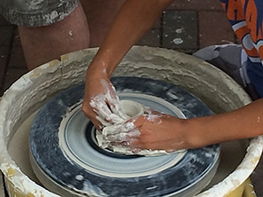 A child's hands throw a pot on a pottery wheel in the demo tent