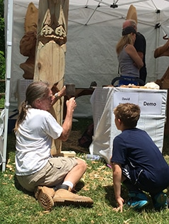 Artist David Shankland demonstrates wood carving while a boy watches