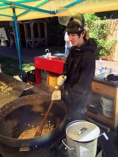 A man in gloves and welder's mask stirs corn in hot oil ready to pop
