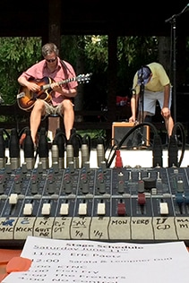 A volunteer adjusts the amplifier while a guitarist warms up, a mixing board and stage schedule in the foreground