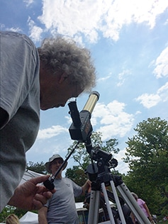 Ian Cooper of the Chagrin Valley Astronomical Society peers through a telescope with a solar filter