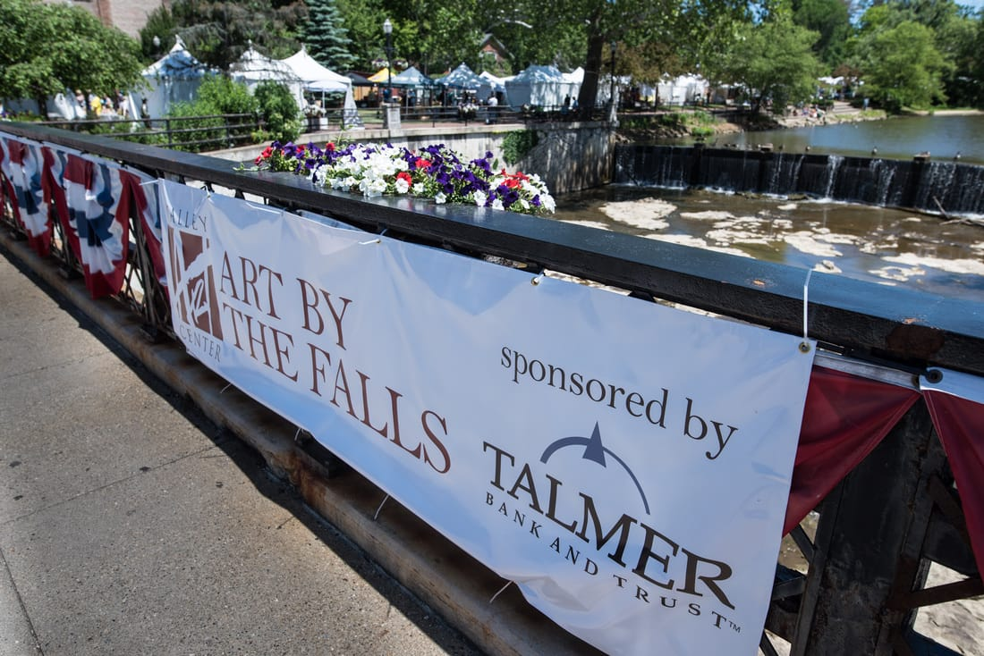 A large banner on the bridge above the Chgrin River reads Art by the Falls sponsored by Talmer Bank and Trust