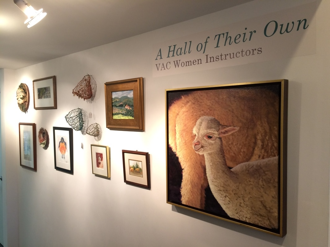 An oil painting of a pair of llamas by Victoria Wagner hangs in the foreground alongside other art pieces in the hallway gallery