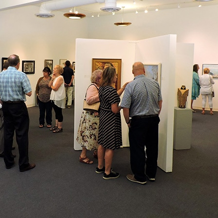 Groups of visitors view the art on display in the gallery in summer 2017