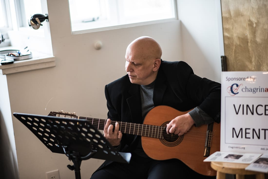 Vince Menti performs classical guitar at an exhibit opening reception