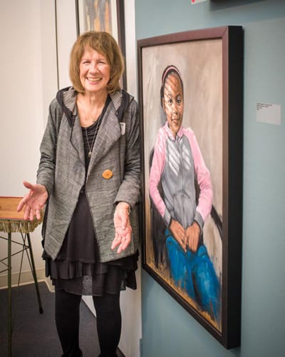 An artist poses next to her award-winning painting in the gallery