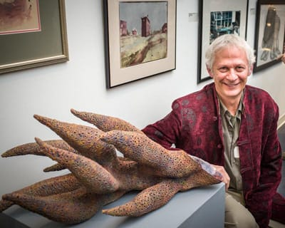 An artist poses next to his award-winning sculpture in the gallery